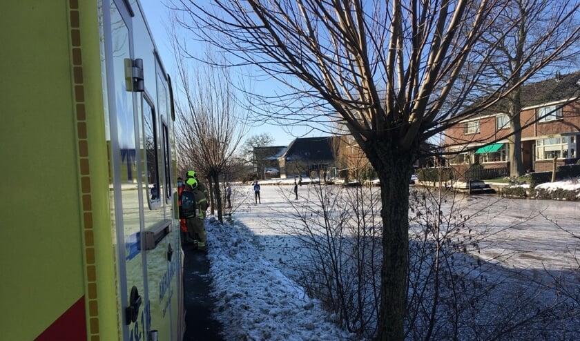 • De ambulance staat langs de Dorpsstraat, schaatsers kijken verschrikt toe.