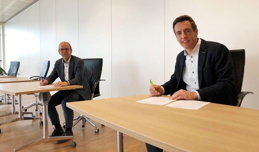 <p>Wethouder Hans Tanis en projectontwikkelaar Van Daalen ondertekenen de overeenkomst voor de bouw van de Poort van Woudrichem.</p>