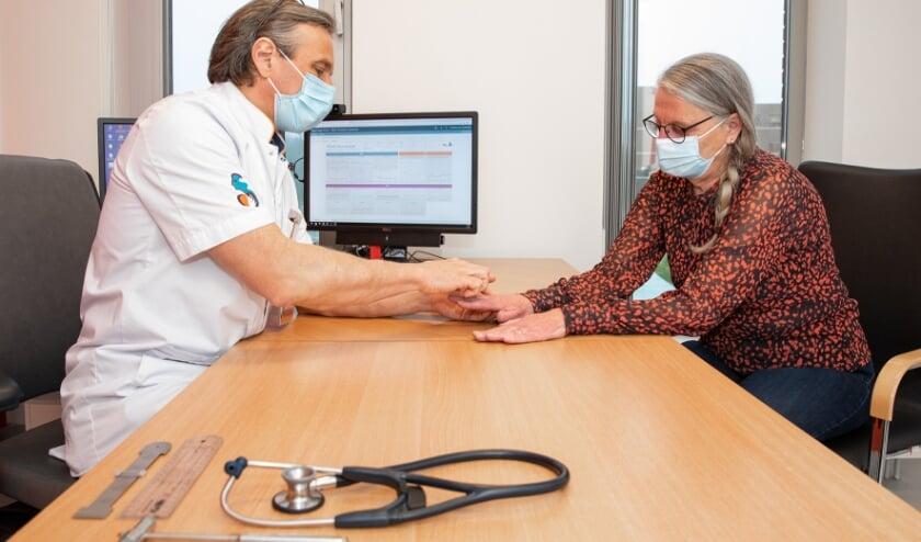 <p>• Reumatoloog Ilja Tchetverikov bekijkt met Klarie Stigter, de 800e onderzoeksdeelneemster, de gevolgen van artritis psoriatica in haar handen.</p>