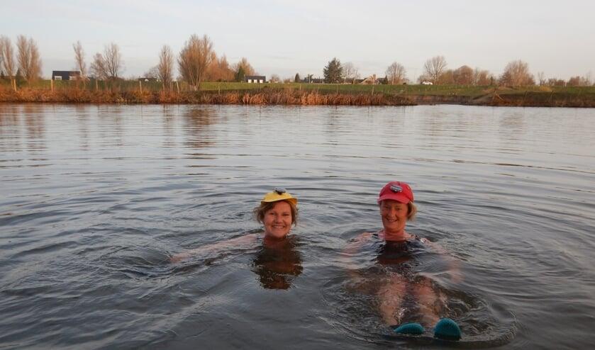 • Annemieke Kleen (l) en Pauline Vrij in het koude Lingewater met 'verlichte' pet voor de veiligheid.