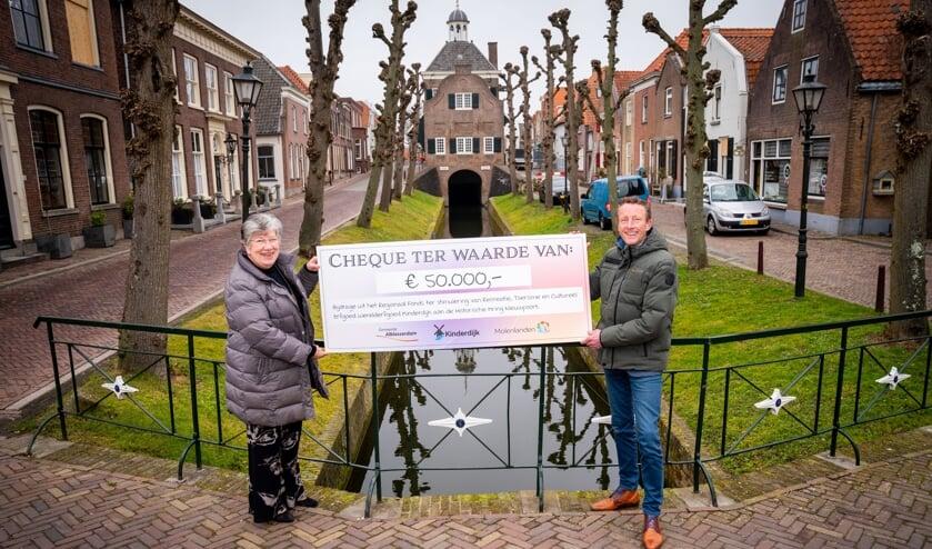 • Arco Bikker reikt de cheque uit aan Adrie den Hartog.