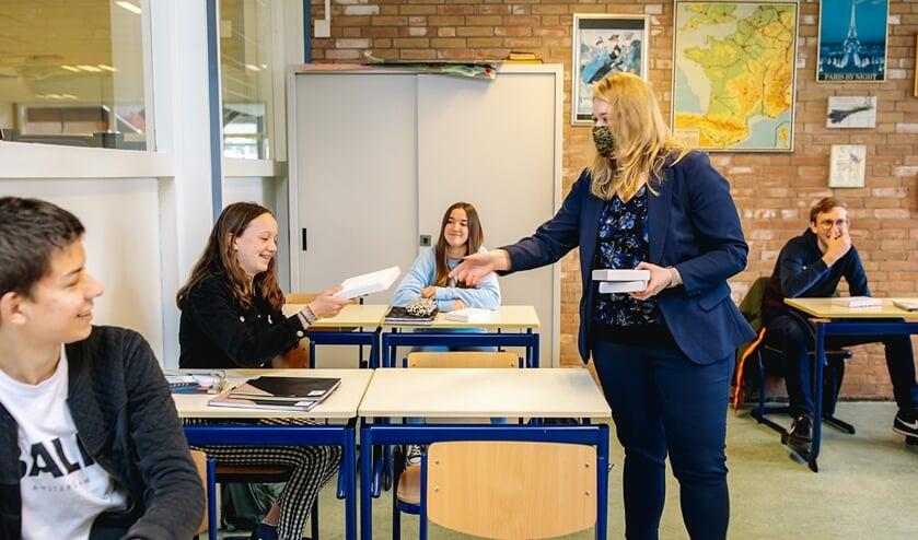 • Mevrouw D. Smits, docent Frans geeft pakketje aan Tessa Knauf, atheneum 3.