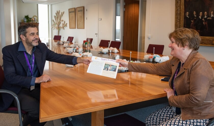 • Bestuurslid Heleen Roos van Hospice De Cirkel overhandigt de eerste jubileumjaarkrant aan ziekenhuisdirecteur Peter van der Meer.