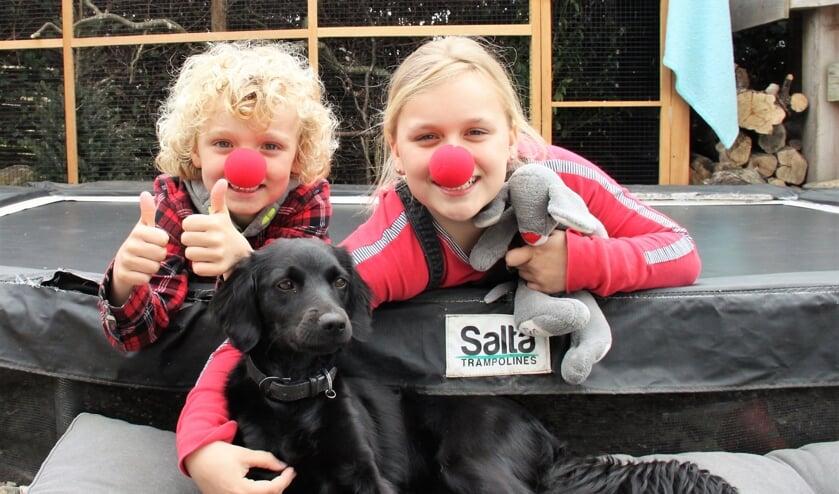 • Levi en Isa Hartmans met hun hondje op de trampoline.