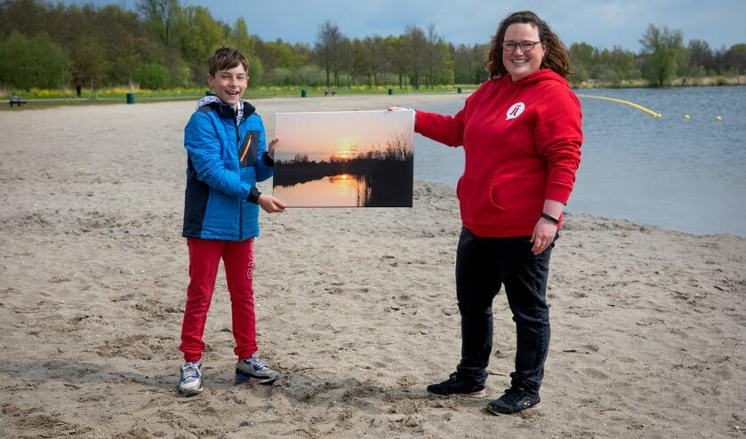 <p>&bull; Kyan van Opstal ontvangt zijn prijs uit handen van jongerenwerker Moniek Boom.</p>