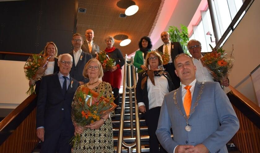 <p>• De groepsfoto met achteraan links de heer Dijkshoorn en zijn partner, achteraan rechts de heer Oral en zijn partner, midden links de heer Van Det en zijn partner, midden rechts mevrouw Noorlander-Eskes en haar partner, vooraan links de heer Kranendonk en zijn partner en vooraan rechts burgemeester Jaap Paans.</p>