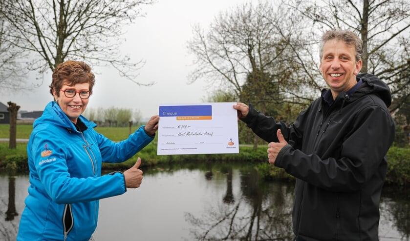 <p>• Corrie de Kluijver overhandigt de cheque aan Francis van der Grijn.</p>