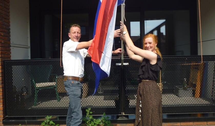 • Wethouder Bikker en huurder Lianne de Haan steken de vlag uit.
