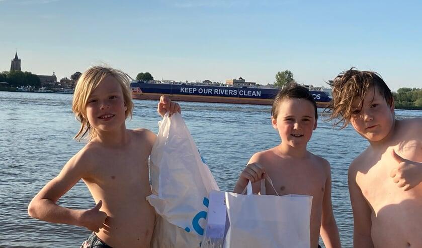 <p>Maas, Dex en Mika met een stranddag afval en op de achtergrond het schip met toepasselijke boodschap.</p>