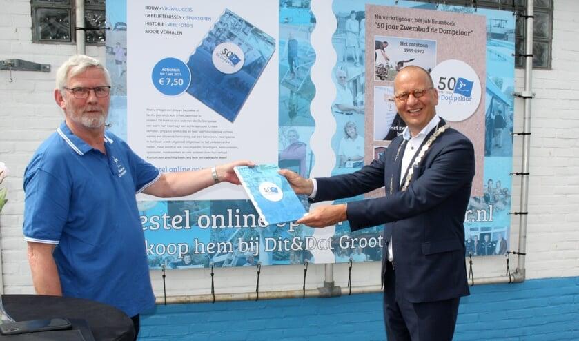 • Burgemeester Segers ontvangt uit handen van Peter Kwakernaak, voorzitter stichting Vrienden van de Dompelaar, het eerste exemplaar van het jubileumboek over 50 jaar zwembad de Dompelaar in Groot-Ammers.