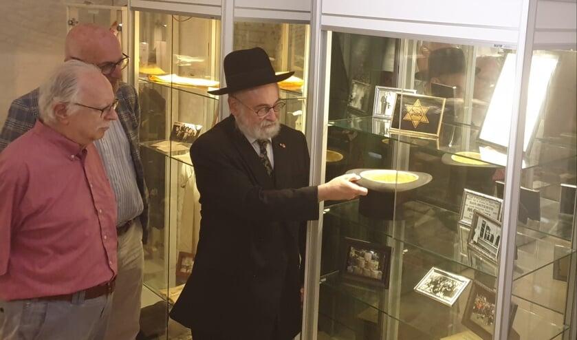 <p>Opperrabbijn Jacobs plaatst de hoge hoed van Bernard van Straten in de vitrine, onder toeziend oog van neven Harvey en Lex van Straten.</p>