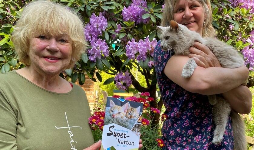• Tineke de Nooij (L) en Miranda Heijdra (R) met Mac, een van de katten van Tineke.