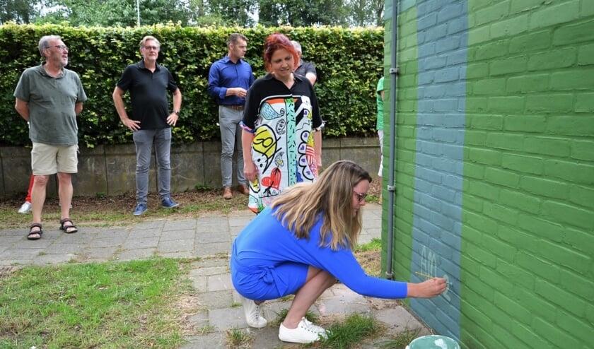 • Wethouder Kamstra legt de laatste hand aan de muurschildering.