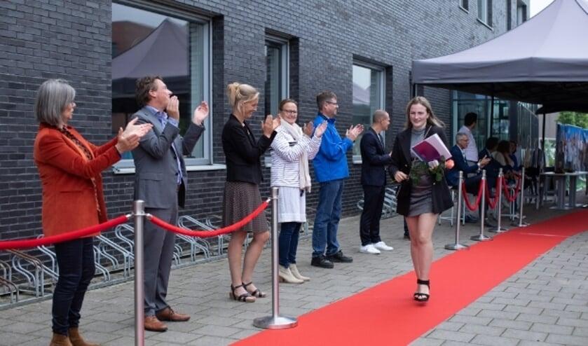 Fleur op de rode loper nadat ze onder luid applaus van havo-directeur Luuk van Beers (tweede van links) en zijn team haar diploma in ontvangst heeft genomen.
