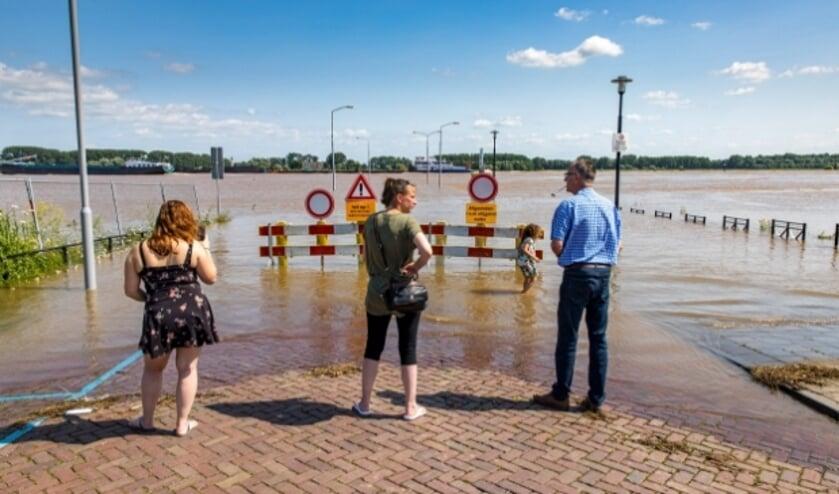 <p>De hoge waterstand van de Waal in juli 2021 trekt veel kijkers bij de Veerweg in Tiel. De pont vaart nog. Foto Jan Bouwhuis.</p>