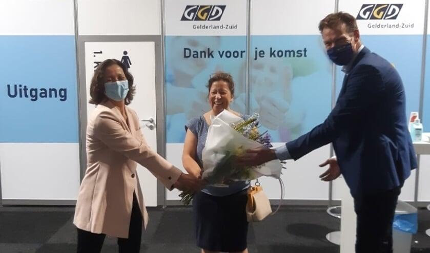 <p>Natasja Lammers (midden) ontvangt de bloemen ter gelegenheid van 500.000e vaccinatie door de GGD Gelderland-Zuid.</p>