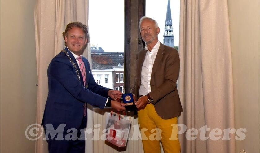 <p>Robert Kreder krijgt de vrijwilligerspenning uitgereikt door bgm Pieter Verhoeve</p>