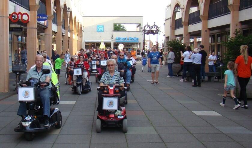 <p>Scootmobielers van Flipje op Wielen rijden tijdens de avondvierdaagse winkelcentrum Passewaaij binnen.</p>