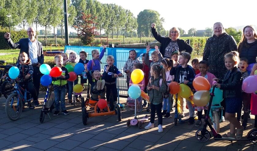 Wethouder Hans Tanis met de jongste kinderen van de Prins Willem Alexanderschool en kinderdagverblijf De Schat in Eethen.