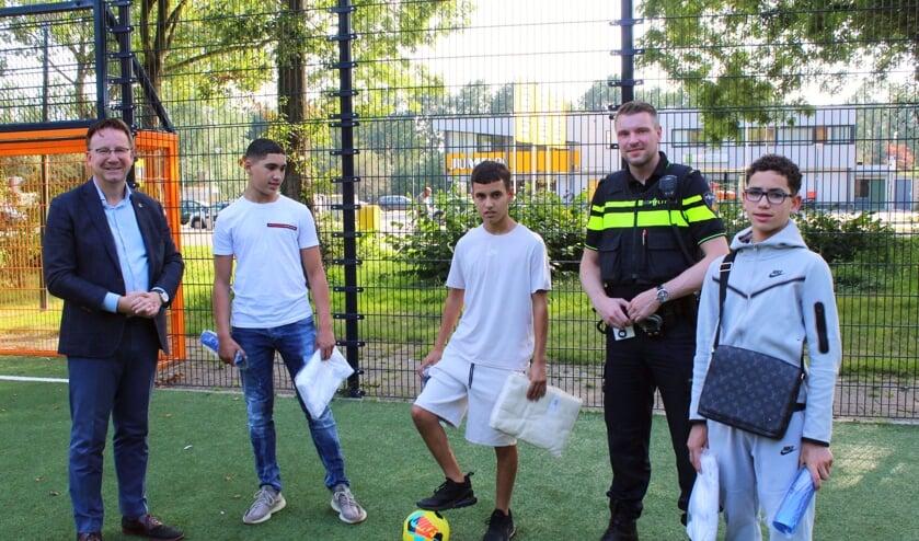 <p>Drie van de vier jonge helden met burgemeester en politie.</p>