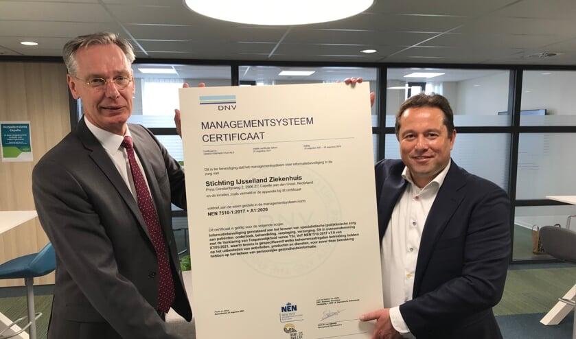 Bestuurder Albert van Wijk (links) neemt het NEN7510 certificaat in ontvangst uit handen van Chris de Back van DNV.