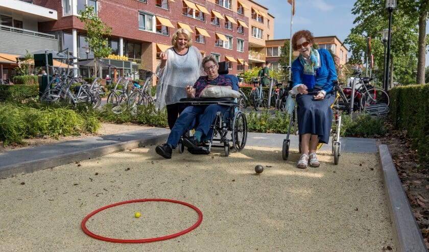 <p>Welzijnsmedewerker Natascha van Empel begeleidt bewoners van Woonzorgcentrum Walstede bij hun balspel op het jeu de boules-baantje.</p>
