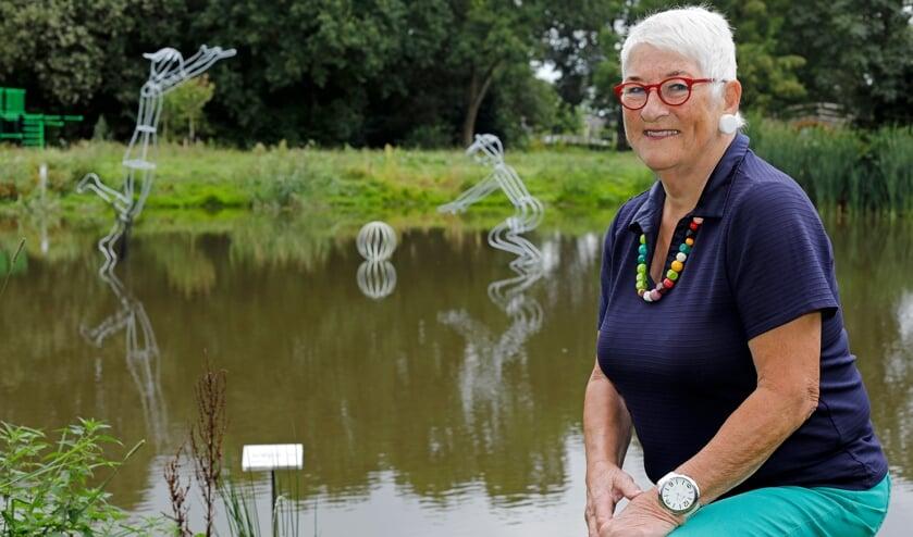 • Kunstenaar Saskia Fluks, met achter haar het door haar gemaakte kunstwerk in de vijver.