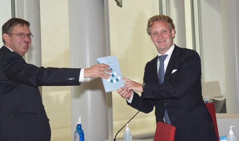 <p>Peter van den Berg overhandigt het eerste exemplaar.aan Pieter Verhoeve</p>