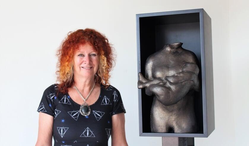 Carrie Jansen voor het beeld van een moeder met kind.