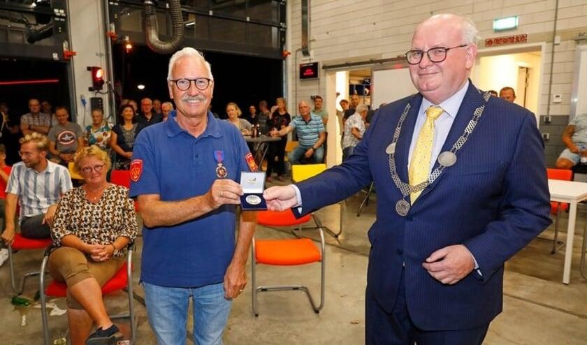 Brandweerman Gerard Koekman ontvangt de Erepenning van burgemeester Frans Backhuijs.