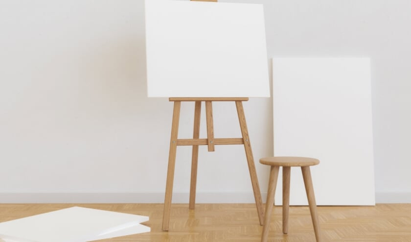 blank canvas on a wooden easel in a bright room with a stool in front of it and several canvases around it. 3d render