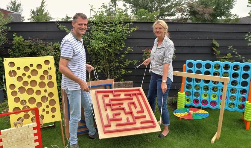 • Kees en Esther Versteeg bij enkele houten speelgoedattributen.