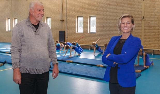 <p>Ad Gerretzen heeft het voorzittersstokje van De Zwols Gymnastiek Vereniging Kwiek en Lenig overgedragen aan Ilse Wienbelt. Op de achtergrond is de jongensgroep aan het trainen.</p>