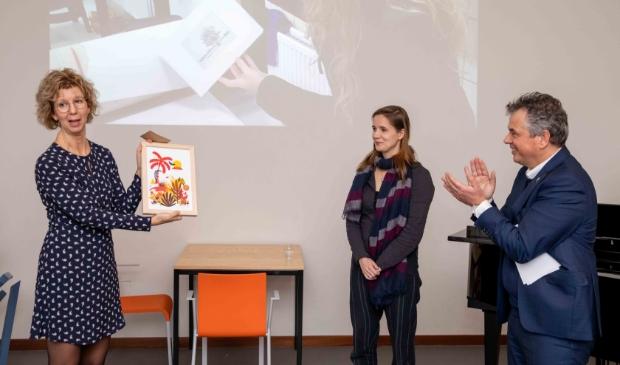 Wethouder Irma van der Sloot ontvangt een unieke kleurenzeefdruk uit handen van kunstenares/docent Kirsten Offringa en Quintusdirecteur Hendrik Jan Houtsma.