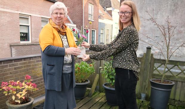 <p>Mevrouw Kroneman ontvangt een bloemetje van Gerla Uilenberg.</p>