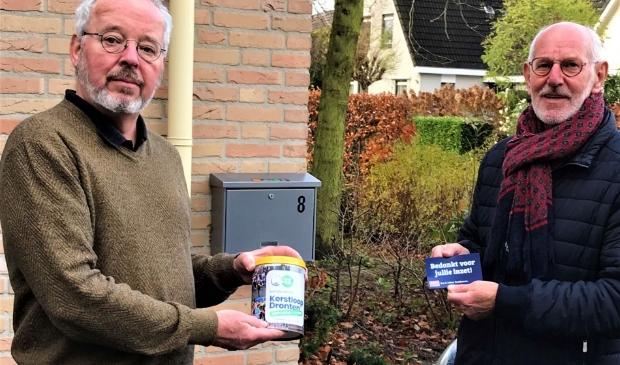 Vrijwilliger Johan Banis ontvangt de koeken uit handen van voorzitter Allert Everts.