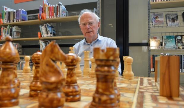 Onno Wolters met het schaakspel in de bibliotheek.
