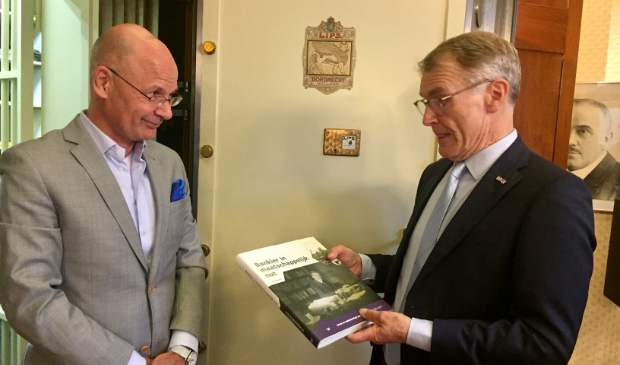 De overhandiging va het boek door Herman Harder aan de grote baas van de Volksbank, Martijn Gribnau.