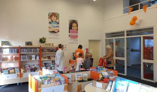 Leesconsulent Marjan Albert en de 2 bibliotheekoma's van het Visnet helpen leerlingen bij het lenen van hun eerste boek uit de nieuwe schoolbibliotheek.