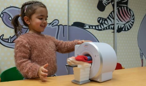 Viënne (3 jaar) onderzoekt hoe de mini MRI werkt.