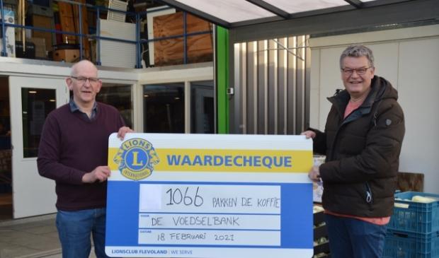 Dick van Tilburg overhandigt de cheque aan Jan Groenendijk van de voedselbank.