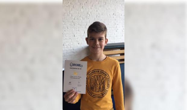 Gerson van der Maaten ontvangt de oorkonde n.a.v. de voorleeskampioenschappen op de Koldewijn Schoele uit Kamperveen