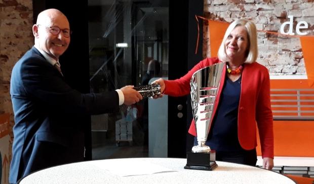 <p>Bort Koelewijn overhandigt de luxe pennenset aan Margriet Roukema met voor zich de wisselbeker voor de teams</p>