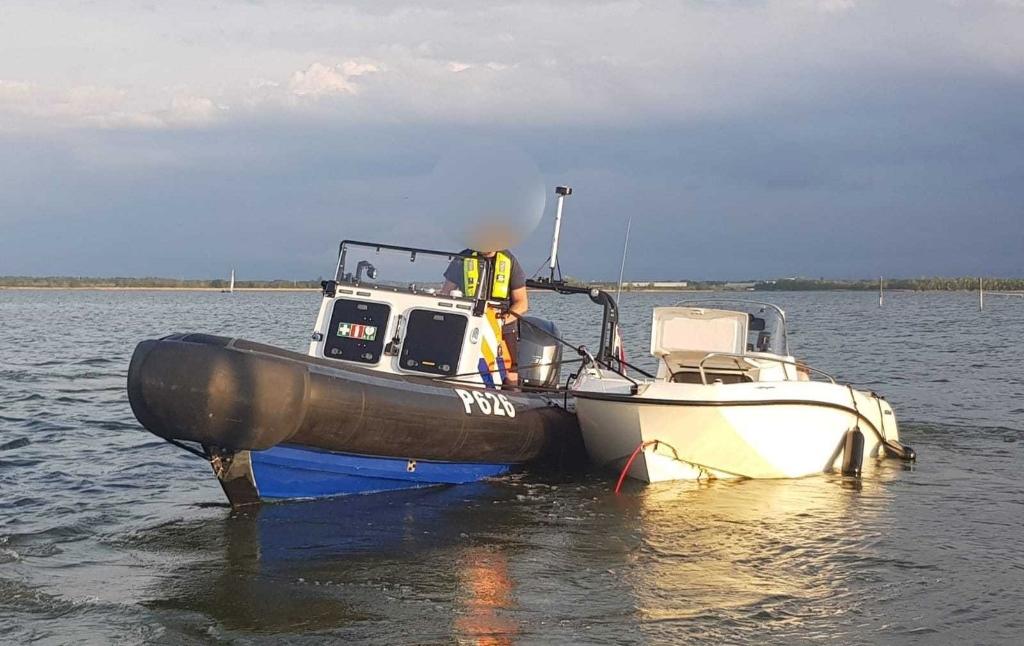De speedboot wordt door de politie naar de kant gebracht.