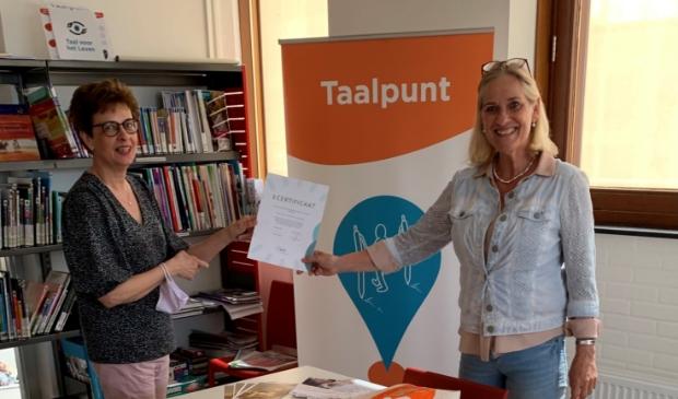 Bibliotheekdirecteur Hetty van de Weg en Taalpuntdocent Barrie Nitrauw tonen trots het behaalde certificaat