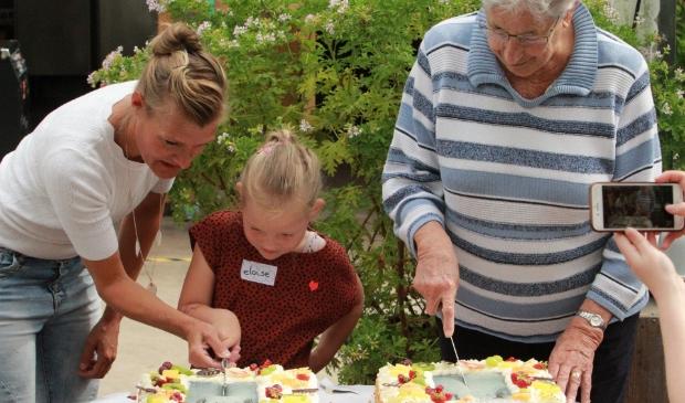Eloïse en mevrouw Boonman snijden de taart aan
