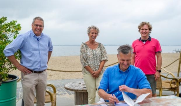 Notaris mr. Erik de Jonge tekent de oprichtingsakte terwijl het bestuur van de nieuwe roeivereniging goedkeurend toekijkt.<br><br> Michael C. Meijburg © BrugMedia