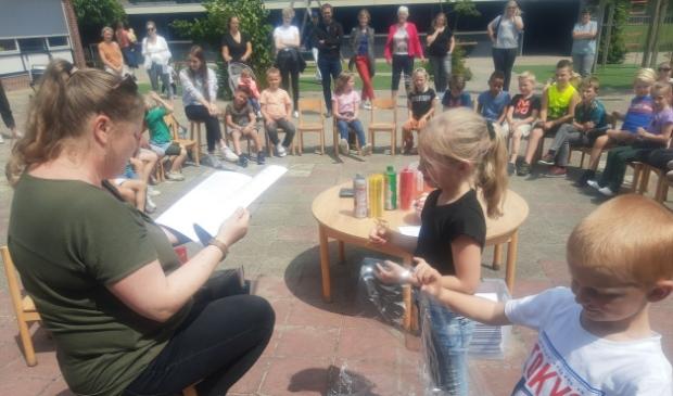 Twee leerlingen van De Fontein overhandigen het eerste exemplaar van de verhalenbundel