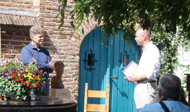 Peter Voerman (links) heeft in het museum het eerste exemplaar van 'Gevangen in een paradijs' aan wethouder Auke Schipper.