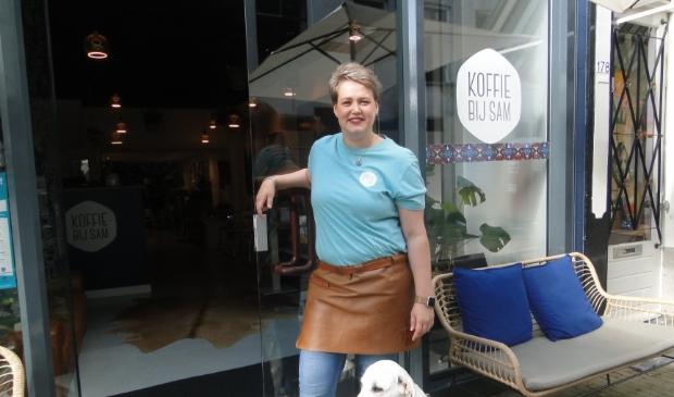 Op de foto: Sam en de hond Boyd voor de ingang van Koffie bij Sam